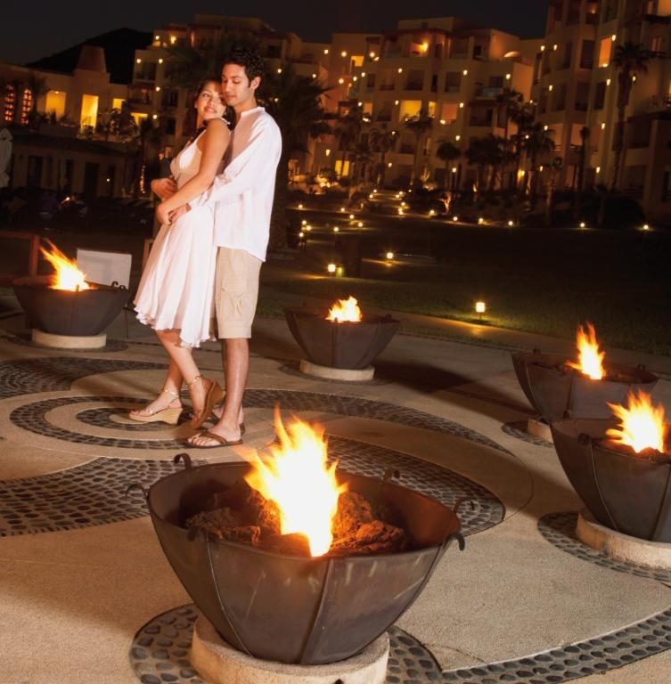 Couple hugging at resort hotel at night, Los Cabos, Mexico