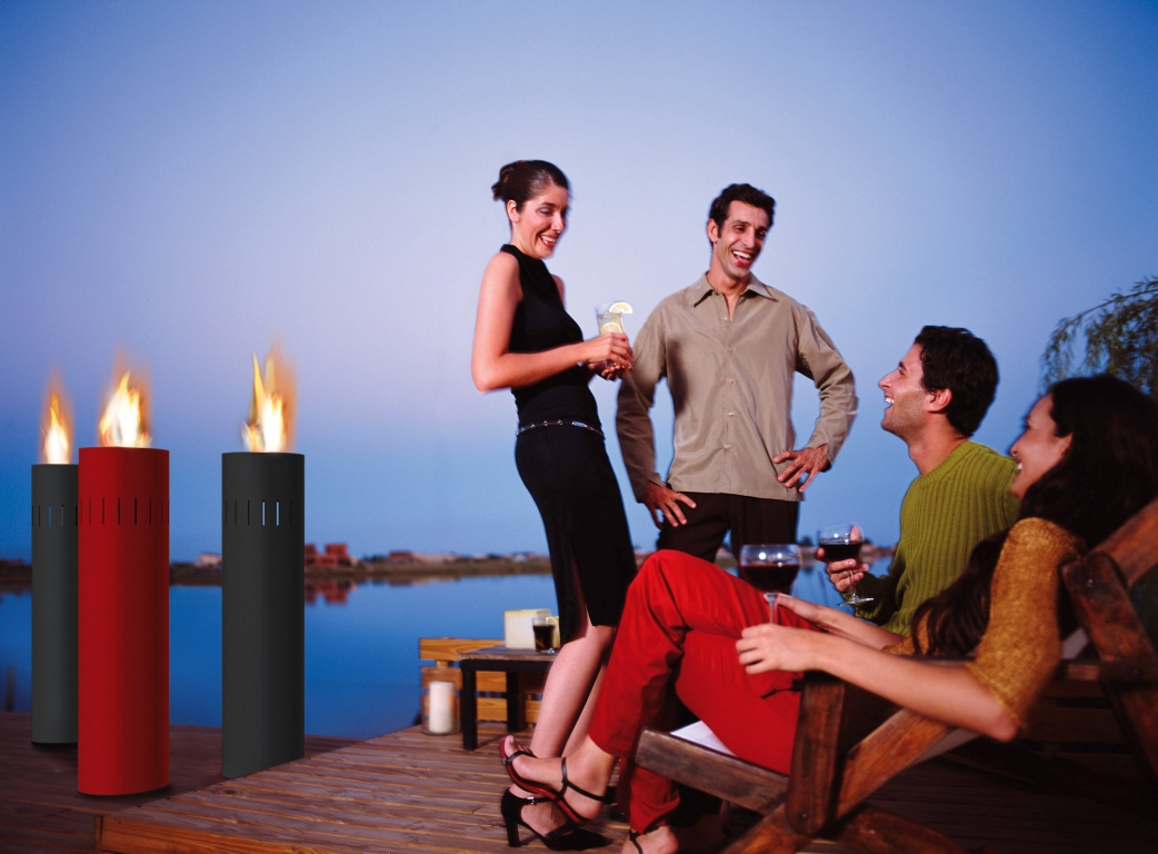Four young adults drinking wine and cocktails on deck, sunset